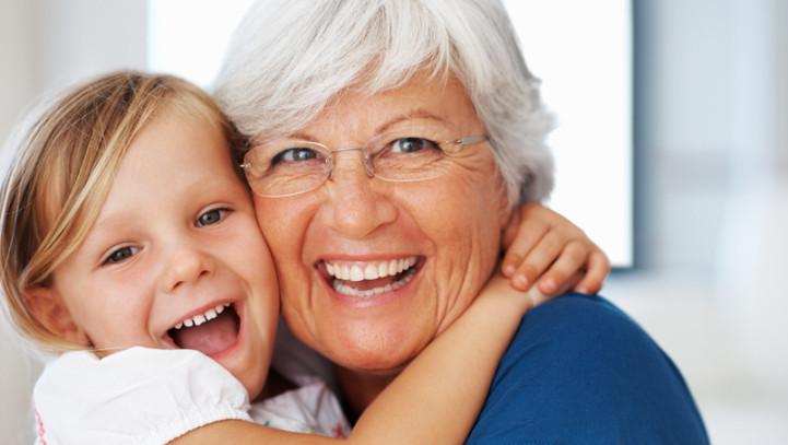 Closeup portrait of senior Caucasian woman hugging cheerful little granddaughter